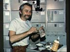 Astronaut Owen Garriott Reconstitutes a Pre-packaged Container of Food